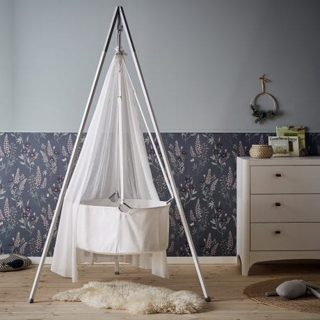 Cute baby nursery with white Leander cradle in tripod and white Leander dresser