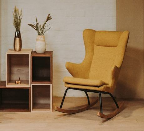Quax rocking nursing chair in mustard coloured fabric in neutral room